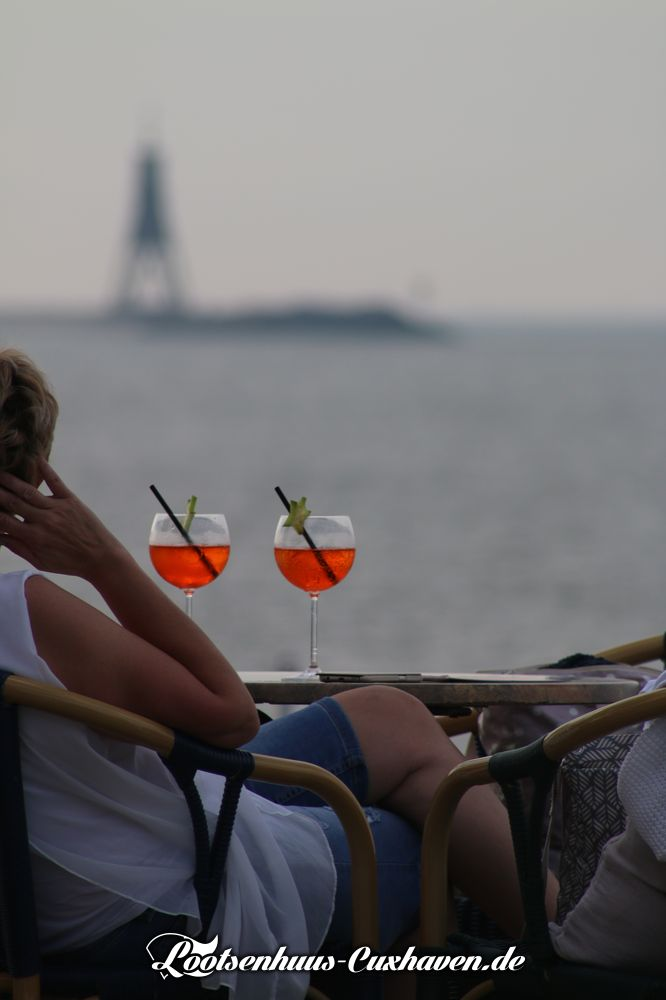 Grimmershörnbucht im Sommer, Gläser auf Tisch, Kugelbake im Hintergrund, in Cuxhaven