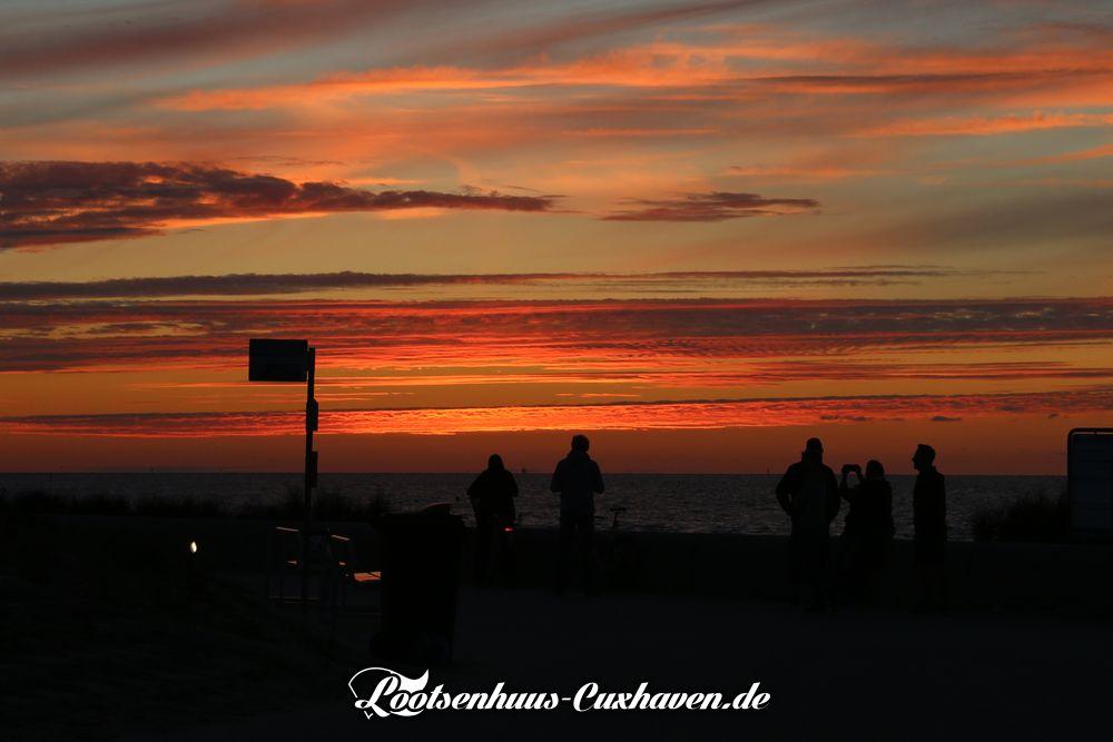 Sonnenuntergang an der Kugelbake mit Blick auf die Nordsee, roter Himmel in Cuxhaven